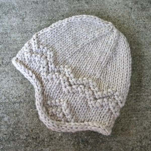 Free knitting pattern for an adult's earflap hat, knit in bulky weight wool.